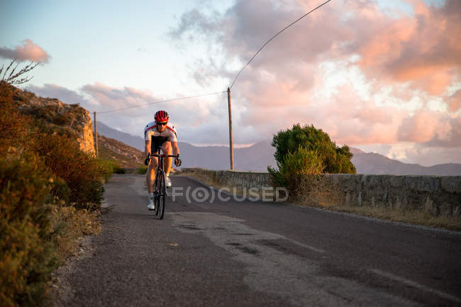 Дорожный велоспорт над морем на закате — стоковое фото