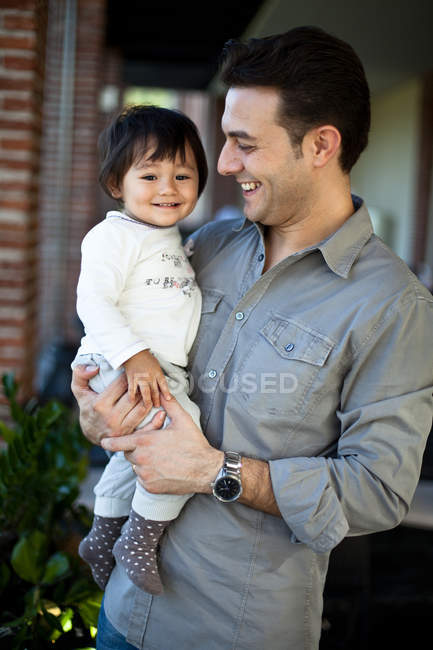 Padre sosteniendo hija en las manos - foto de stock