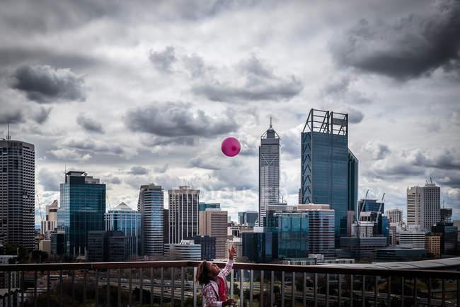 Menina jogando balão no ar — Fotografia de Stock