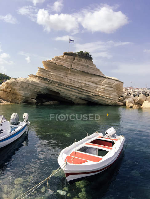 Scenic view of rocky coast and boats moored in foreground, Zakynthos, Greece — Stock Photo