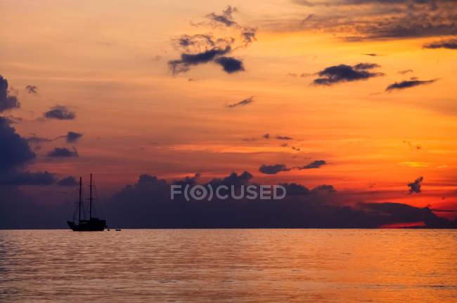 Beau soleil couchant ciel, mer et bateau sur l'eau — Photo de stock