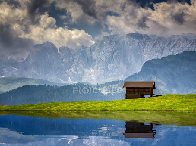 Beautiful rocky mountains landscape, wooden hut in meadow — Stock Photo