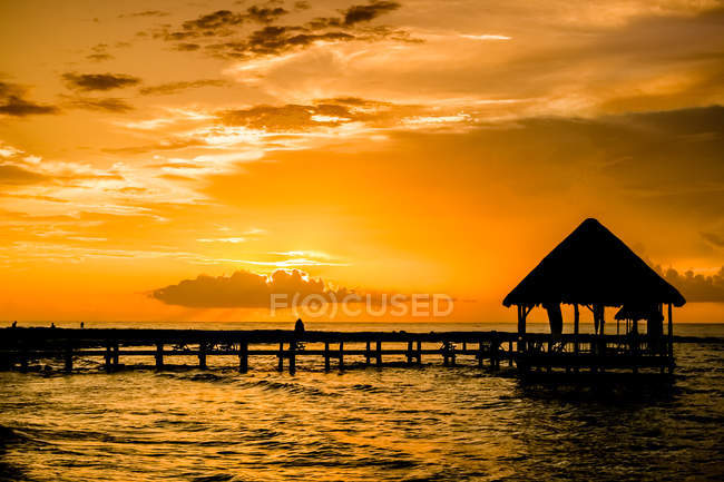Beautiful orange sunset sky, sea water with pier and small hut — Stock Photo
