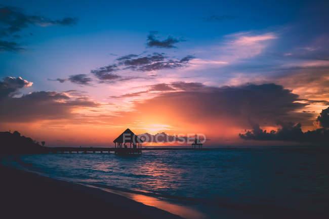Cielo hermoso atardecer, agua de mar y pequeña casa en el muelle - foto de stock