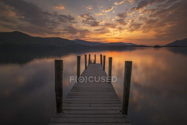 Красивое небо заката и пирс на озере — стоковое фото