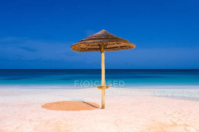 Tropical resort, sandy beach with umbrella at sea water — Stock Photo