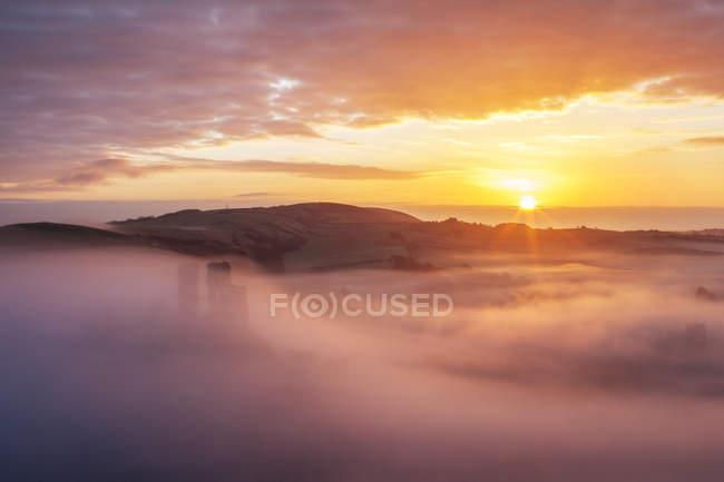 Beau ciel couchant et collines dans les nuages — Photo de stock