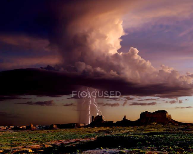 Une cellule orageuse imposantes, se déplaçant sur Monument Valley, à la frontière de l'Utah et l'Arizona près de coucher du soleil, é.-u. — Photo de stock