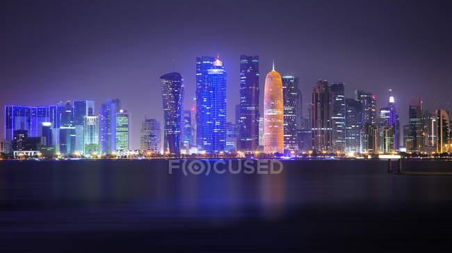 Vista del horizonte de Doha a lo largo de la bahía de Doha por la noche en Qatar - foto de stock