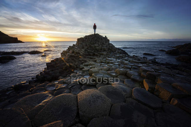 Woman standing on Giants Causeway at sunset, County antrim, Irlanda do Norte, Reino Unido — Fotografia de Stock