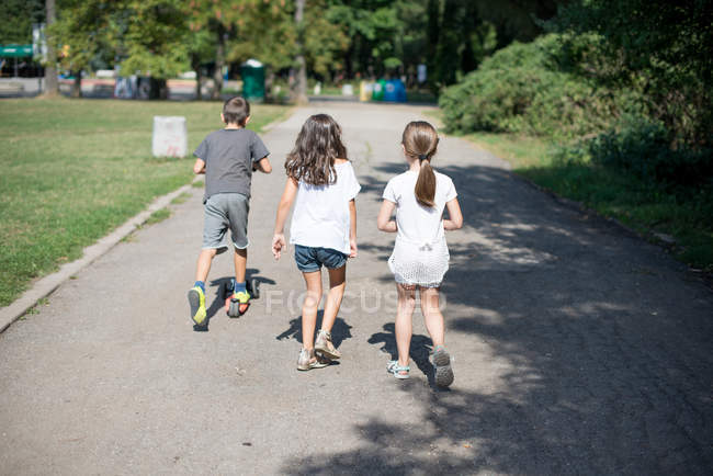 Drei Kinder laufen Fußweg im Park entlang — Stockfoto