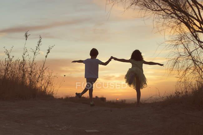 Девочка и мальчик держатся за руки, танцуют на закате — стоковое фото