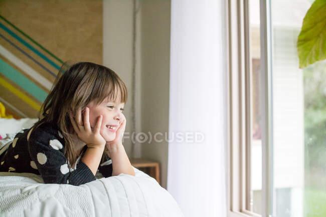 Портрет улыбающейся девушки, лежащей на кровати — стоковое фото