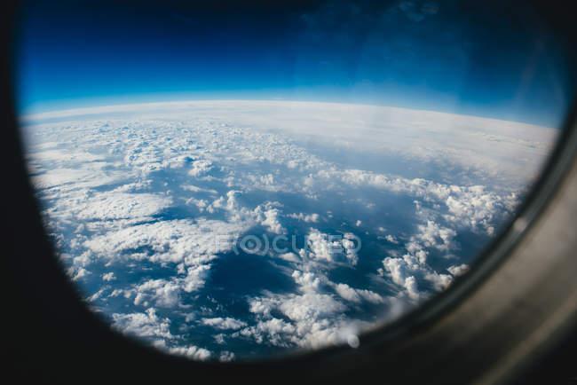 Nuvens através de uma janela de avião — Fotografia de Stock
