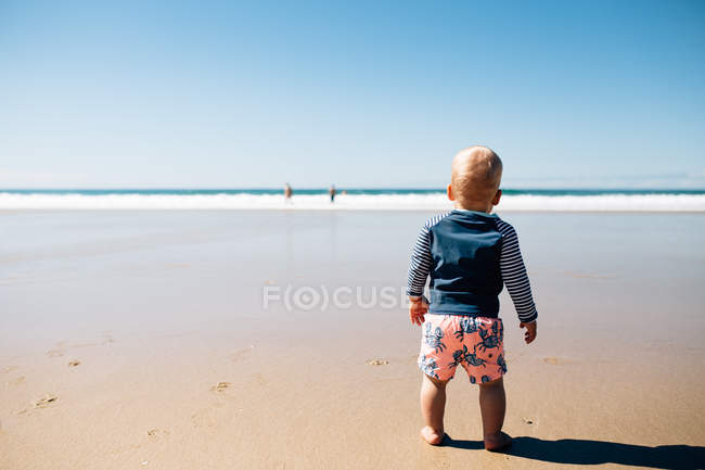 Мальчик стоит на пляже, Нуса Хэдс, Квинсленд, Австралия — стоковое фото