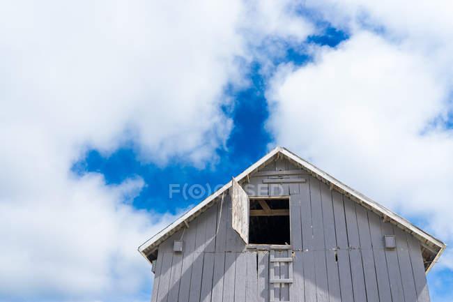 Bajo ángulo de una casa bajo el cielo nublado azul - foto de stock