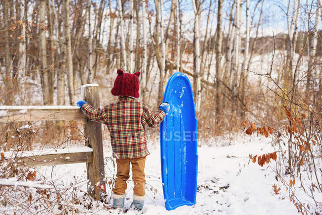 Boy standing in snow holding a sledge — Stock Photo