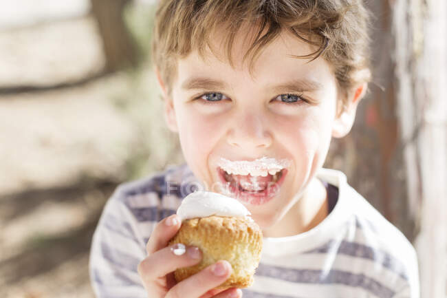 Niño comiendo un cupcake en la naturaleza - foto de stock
