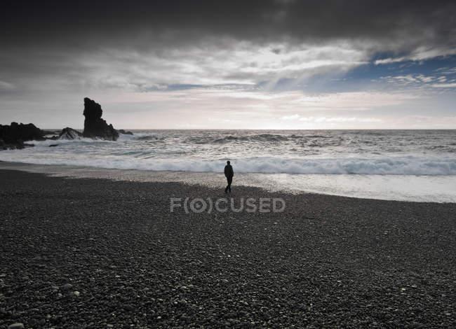 Mann läuft am schwarzen Strand entlang, djupalonssandur, snaefellsnes, iceland — Stockfoto