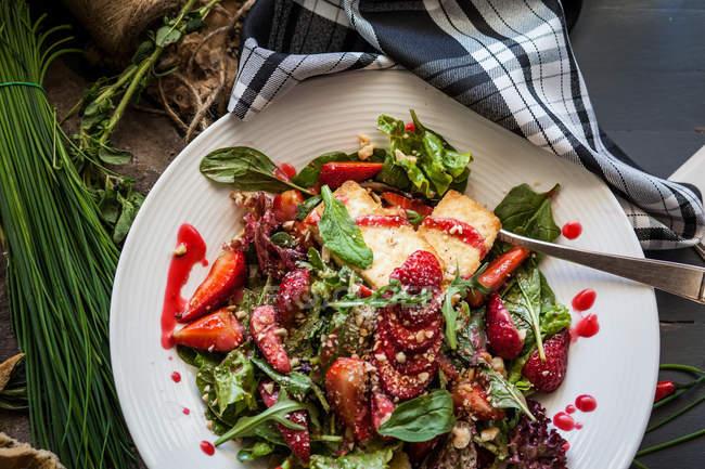 Ensalada de queso de cabra, fresa y rúcula en plato blanco - foto de stock