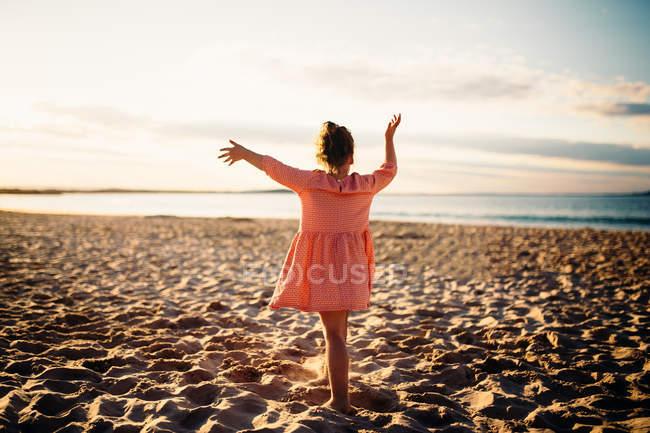 Ragazza in piedi sulla spiaggia danza, vista posteriore — Foto stock
