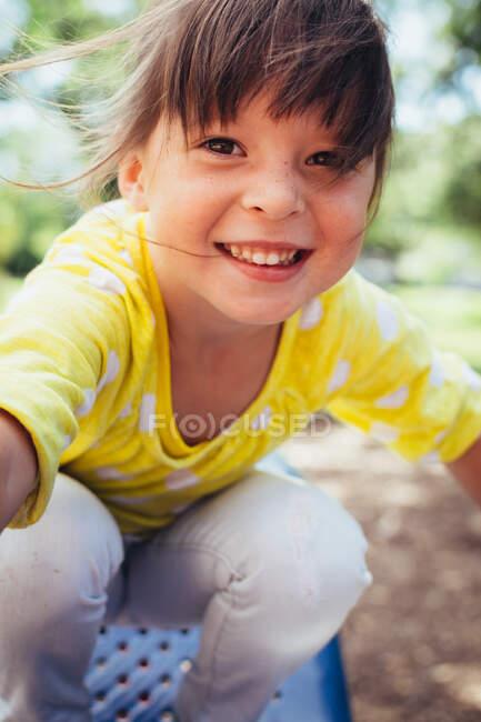 Retrato de una chica sonriente en un parque infantil - foto de stock