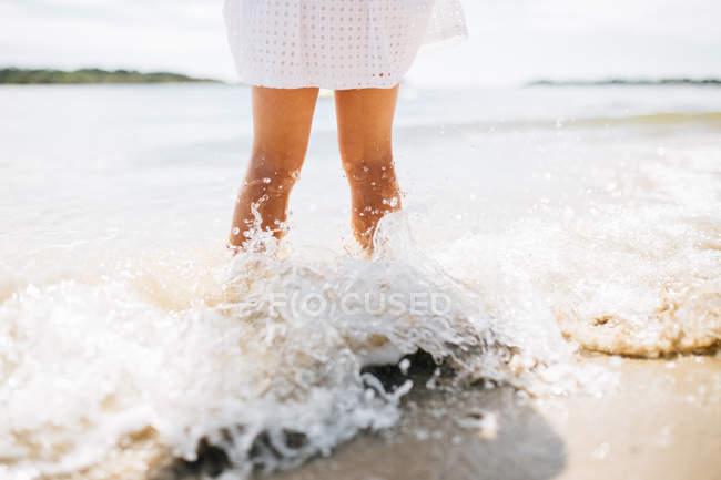 Mädchen, das am Strand steht, mit Wellen, die ihre Beine bespritzen, noosa heads, queensland, Australia — Stockfoto