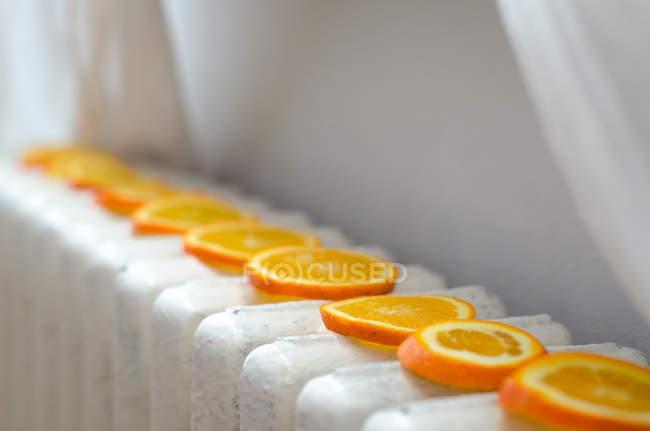 Vista de cerca de rodajas de naranja de secado en un radiador - foto de stock