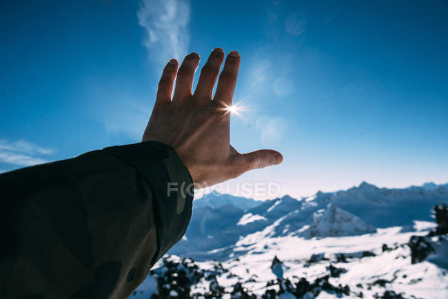 Man hand reaching for sun in mountains — Stock Photo