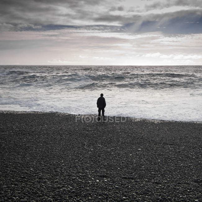 Man standing on black beach looking out to sea, djupalonssandur, snaefellsnes, iceland — Stock Photo