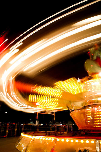 Scenic view of Blurred motion shot of a carousel swing at night — Stock Photo