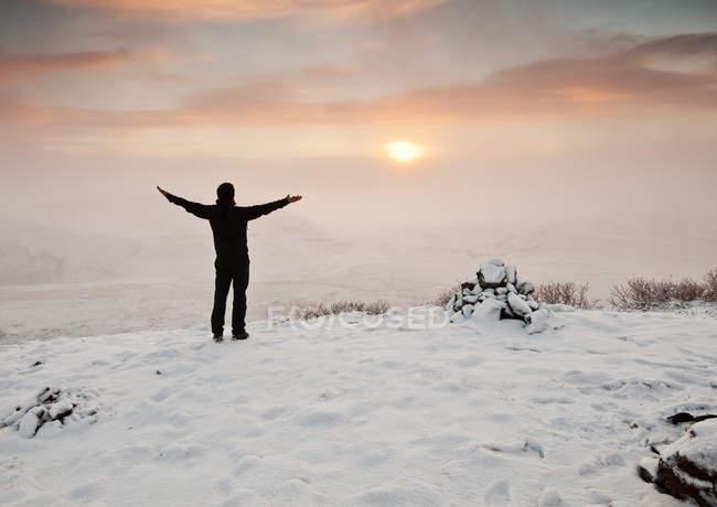Vista trasera de un hombre de pie en el paisaje de invierno, Islandia - foto de stock