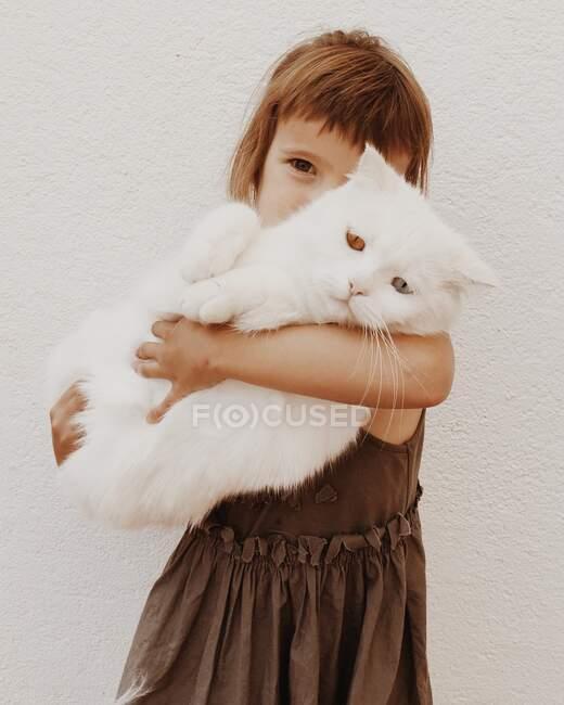 Chica abrazando a su gato mascota con diferentes ojos de colores - foto de stock