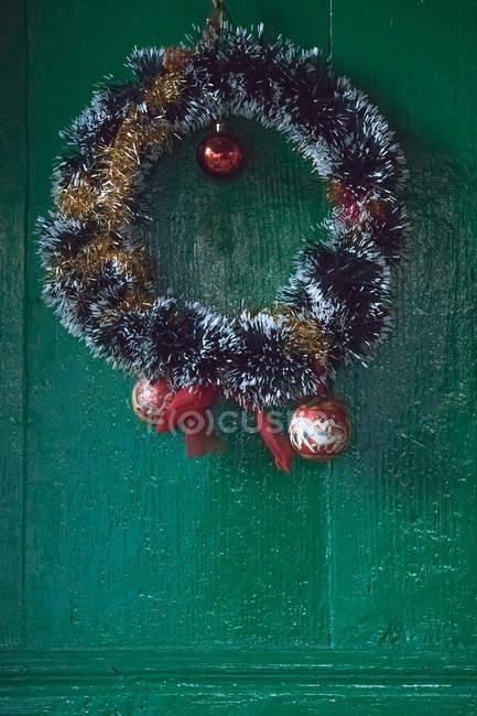 Grinalda de ouropel de Natal com bugigangas em uma porta — Fotografia de Stock