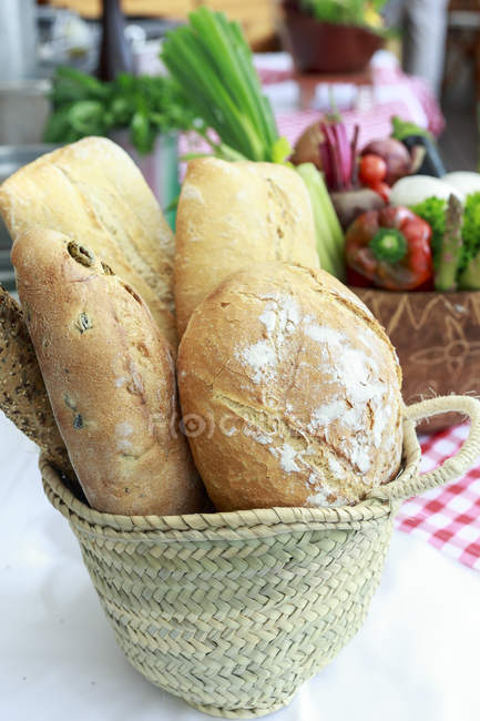 Basket with fresh loafs of bread on table — Stock Photo