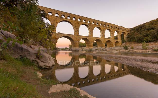 Vista panorámica de las reflexiones del acueducto Pont Du Gard en el río Gardon, Francia - foto de stock