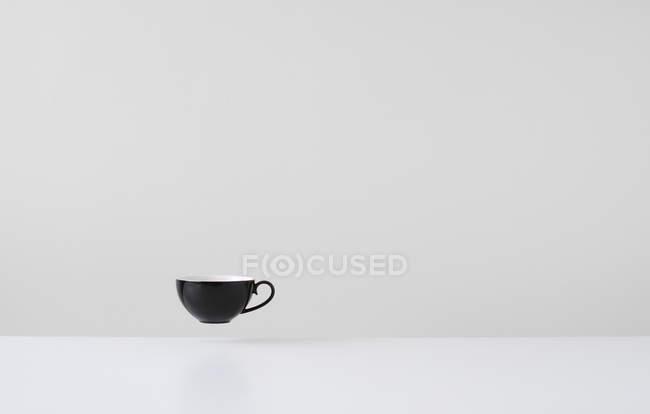 Café negro flotando en medio del aire - foto de stock