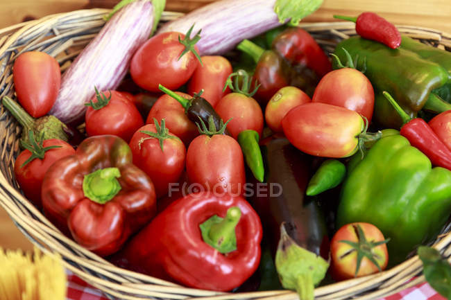Basket with fresh tomatoes, peppers, aubergines and chilies — Stock Photo