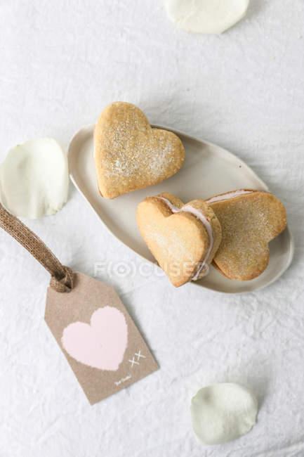 Herzförmige Shortbread-Kekse über weißem Tisch, Draufsicht — Stockfoto