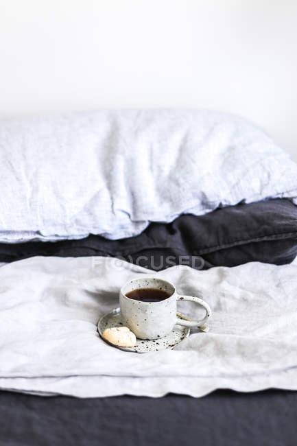 Чашка чая и печенье на кровати — стоковое фото