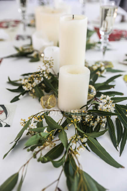 Candles and eucalyptus centerpiece on dining table — Stock Photo