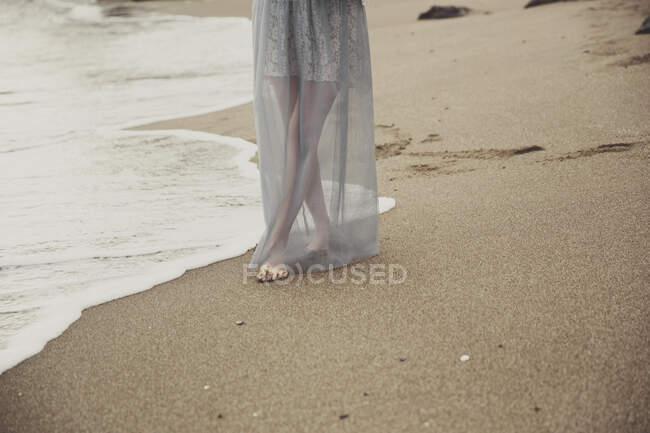 Sección baja de la mujer caminando en la playa - foto de stock