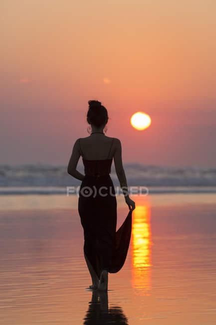 Silhouette de femme en robe sur la plage, Bali coucher de soleil soleil dans le ciel — Photo de stock