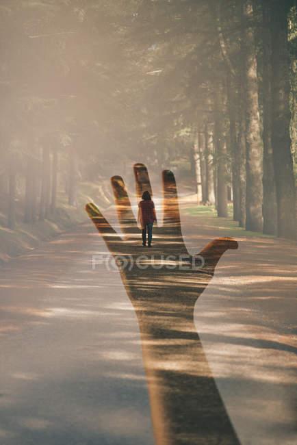 Doble exposición de una mano y una mujer alejándose - foto de stock