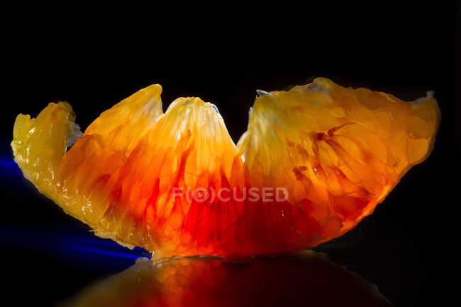 Vista de cerca de un segmento de fruta naranja - foto de stock