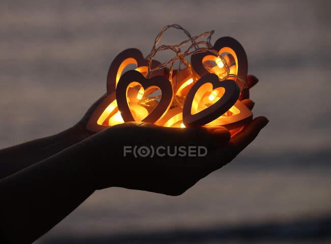 Las manos de la mujer sosteniendo luces de cuerda en forma de corazón - foto de stock