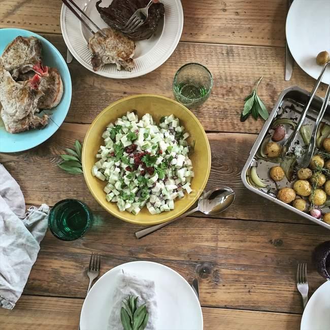 Vista de cerca de patatas asadas con cebolla, ensalada y carne a la parrilla - foto de stock