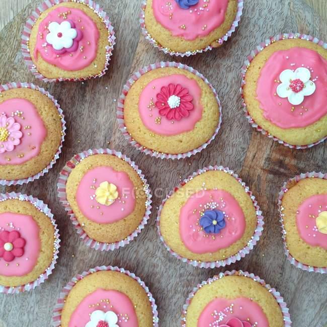 Вид зверху смачні кекси з рожевими глазур — стокове фото