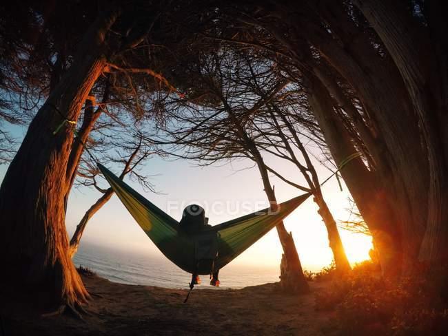 Ragazzo seduto su un'amaca guardando Oceano Pacifico, California, America, Stati Uniti — Foto stock
