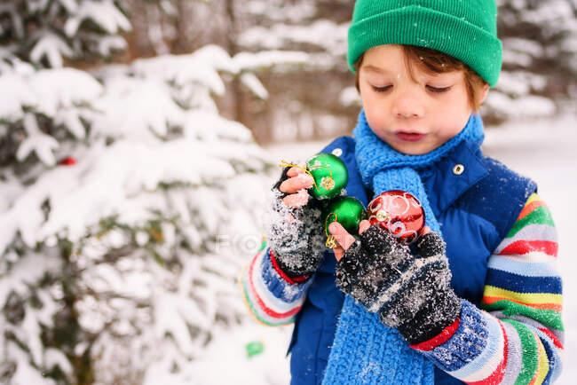 Boy holding Christmas decorations — Stock Photo